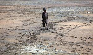 A Turkana törzshöz tartozó fiú áll egy kiszáradt folyómederben az észak-kenyai Lodwar közelében Fotó: Christopher Furlong / Europress / Getty